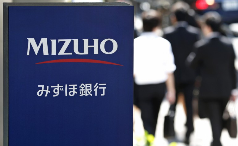 Signage for Mizuho Bank Ltd. is displayed as pedestrians walk past a branch in Tokyo, Japan, on Wednesday, May 15, 2013. Japan's three biggest banks led by Sumitomo Mitsui Financial Group Inc. forecast earnings will decline this year as monetary easing makes loans less profitable even as borrowing picks up amid an economic recovery. Photographer: Kiyoshi Ota/Bloomberg